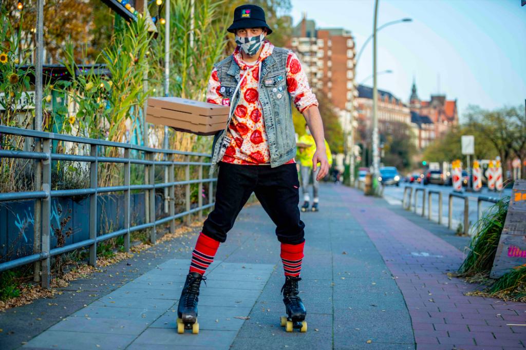 Deine ÜberQuell Pizza wird dir auf Rollerskates geliefert.